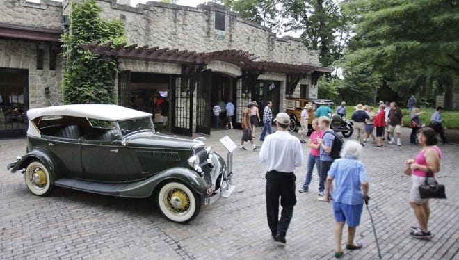 Hundreds gather at the old Merchandising School building to check out a historic auto exhibit during the Henry Ford 150th birthday celebration at the Ford estate - Fair Lane in Dearborn, Mich., on Saturday, July 27, 2013.