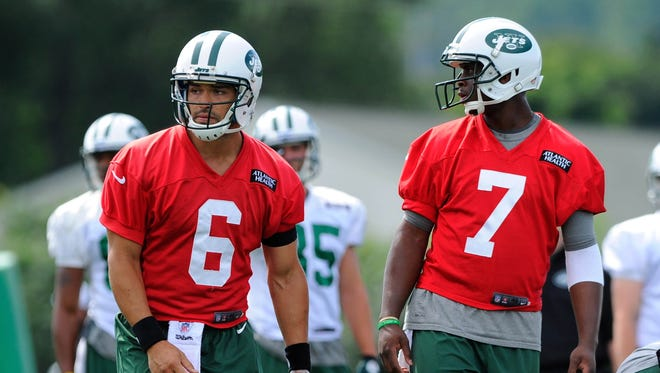 New York Jets quarterbacks Mark Sanchez (6) and Geno Smith (7) look on during training camp at SUNY Cortland.