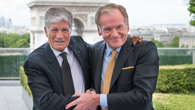 Publicis Group CEO Maurice Levy, left, embraces Omnicom Group CEO John Wren during a press conference on Sunday in Paris.