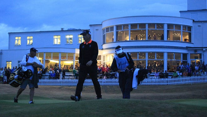 Bernhard Langer of Germany leaves the 18th green in the fading light at Royal Birkdale.