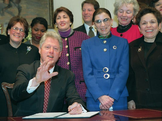 President Clinton gestures in the Oval Office of the White House Tuesday, March 19, 1996, after signing a proclamation designating March as Women's History month. Behind the president, from left are, Deputy White House Chief of Staff Evelyn Lieberman, First lady Hillary Rodham Clinton's Chief of Staff Maggie Williams, Deputy Attorney General Jamie Gorelick, Vice President Gore, Supreme Court Justice Ruth Bader Ginsburg, Deputy Education Secretary Madeleine Kunin, and Health Secretary Donna Shalala. (APPhoto/J. Scott Applewhite) ORG XMIT: WX116