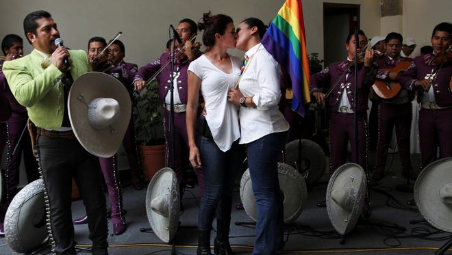 Gay couples celebrate as a mariachi band performs after getting married at a courthouse in Mexico City, July 14, 2013.