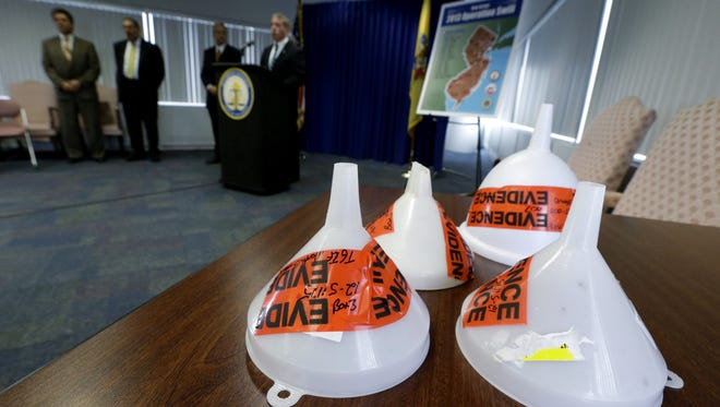 """Funnels confiscated during an investigation dubbed """"Operation Swill,"""" in which 29 bars and restaurants in New Jersey are accused of putting cheap booze in premium brand liquor bottles and selling it, are displayed during a news conference, Thursday, May 23, 2013, in Trenton, N.J."""