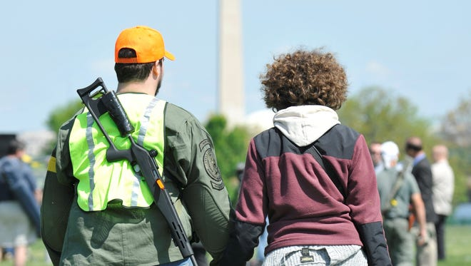 Gun rights advocates gather to publicly carry weapons in a national park across from Washington, D.C., in April.