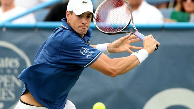 John Isner chases down a backhand return during his second-round victory.