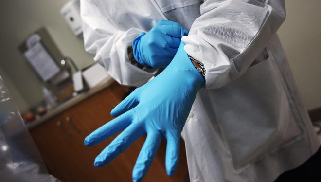 A dentist dons sterile gloves at a community health center in Aurora, Colo., last March. The center, called the Metro Community Provider Network, has received thousands more Medicaid-eligible patients since the health care law was passed in 2010.