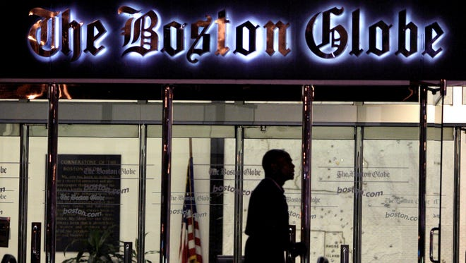 A security guard walks past the entrance of The Boston Globe building in the Dorchester neighborhood of Boston in 2009.