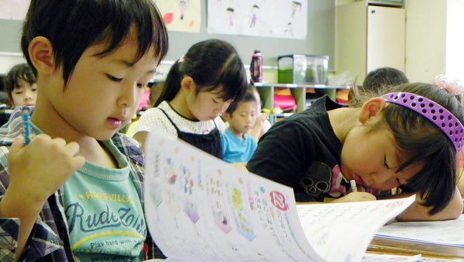 Haruki Niwa, a first-grader at Koyodai Elementary in Inagi, Japan, flips to the next page in his math workbook, which features numbers, Japanese characters and pictures as the foundation for building math skills.
