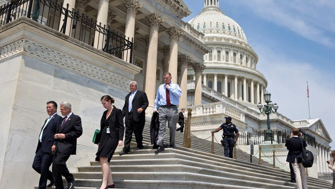 After final votes were cast Friday, lawmakers walk down the steps of the House of Representatives. Congress is now in recess.