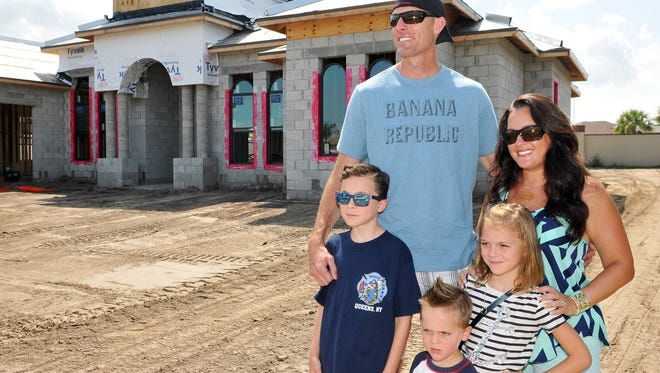 Tom and Mary Beth Corrigan with their children, Matthew, 9, Ryan, 3, and Elizabeth, 7, in front of their new home that is being built in Viera, Fla. The family recently moved to Brevard County, Fla., from Queens, N.Y.