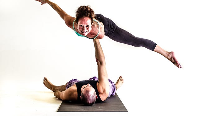 Jessalyn Oxford and Jason Coleman demonstrate AcroYoga, a blend of acrobatics and yoga. They are performing the Bicep Balance pose.