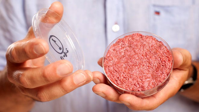 Professor Mark Post of Maastricht University holds the burger he developed from cultured beef in London.