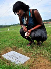 Sylvia Nolan reads her son LeRyan Nicholson's name after his gravestone replaced the marker reading John Doe (#19)  at Bordeaux Cemetary May 30, 2013, in Nashville, Tenn.