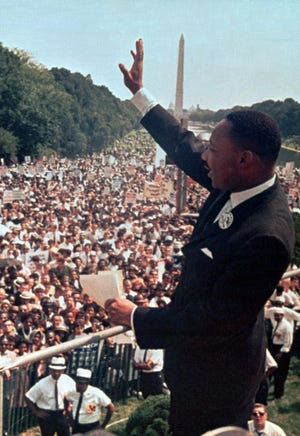 "King waves to the crowd on Aug. 28, 1963, at the Lincoln Memorial during the March on Washington for Jobs and Equality where he delivered his historic ""I Have a Dream"" speech."