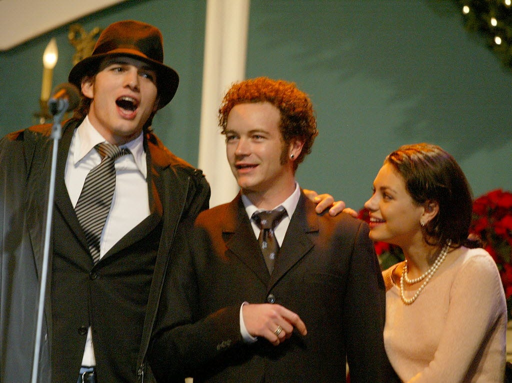 Kutcher, left, Danny Masterson and Kunis perform during the Church of Scientology's 11th annual Christmas Stories fundraiser on Dec. 6, 2003.