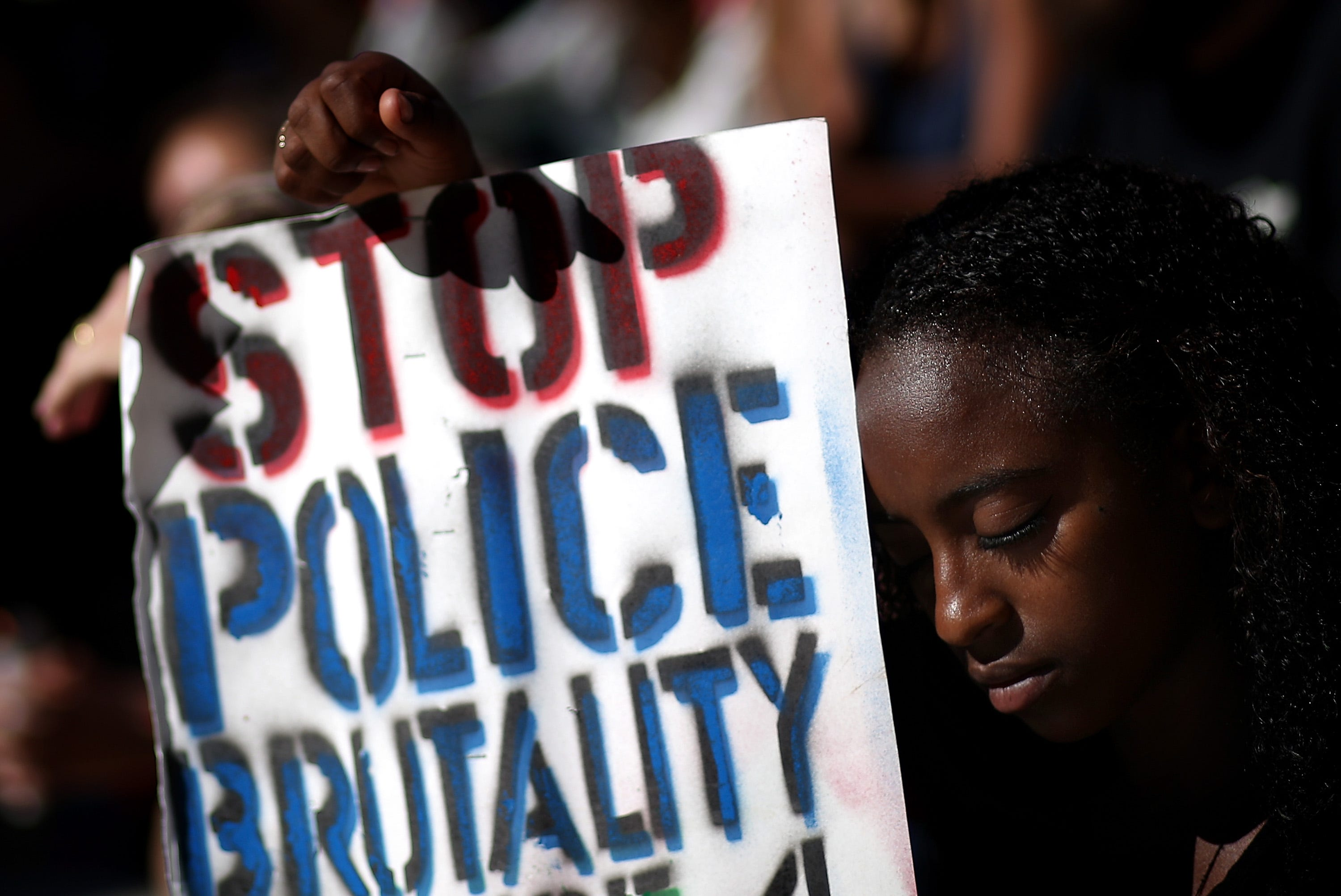 A demonstrator in Oakland, Calif., marks a moment of silence in solidarity with victims of police brutality in August 2014.