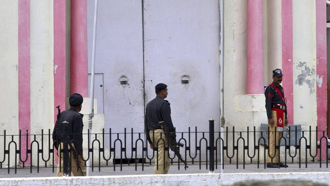 Pakistani police officers stand guard at the main entrance of central prison on the outskirts of Rawalpindi, Pakistan, on Saturday.
