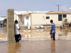 Two men stand in near knee deep water in a mobile home park in Mecca, Calif., after a sudden heavy rain flooded the area early Tuesday.