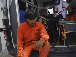 A worker waits to be treated by first responders after an explosion ripped through a gas pipeline distribution center in Reynosa, Mexico near Mexico's border with the United States on Tuesday.