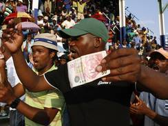 Miners sing and dance whilst holding South African bank notes in Lonmin Platinum Mine near Rustenburg, South Africa, on Tuesday.