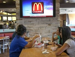 Customers watch the new McDonald's television channel at a McDonald's restaurant in Norwalk, Calif.