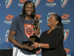 WNBA president Laurel Richie, right, presents Connecticut Sun center Tina Charles with the 2012 WNBA MVP award prior to Game 1 of the Sun's first-round series against the New York Liberty, Thursday in Uncasville, Conn.