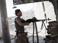 A Free Syrian Army fighter fires at Syrian Army positions during a clash in Aleppo, Syria, Sept. 26, 2012.