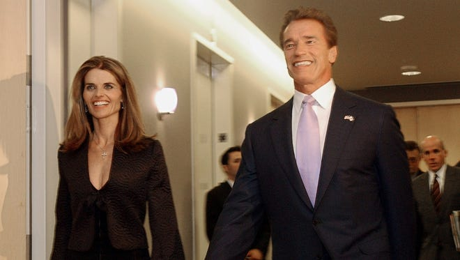 Then Gov.-elect Arnold Schwarzenegger and his wife, Maria Shriver, smile as they walk to a meeting of his transition committee in 2003. In an interview with '60 minutes' scheduled to air Sunday, Schwarzenegger discusses his affair with longtime housekeeper Mildred Baen.