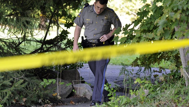 State Trooper Matt Losh emerges from the backyard of a home in New Fairfield, Conn., where the a fatal shooting took place on Thursday.