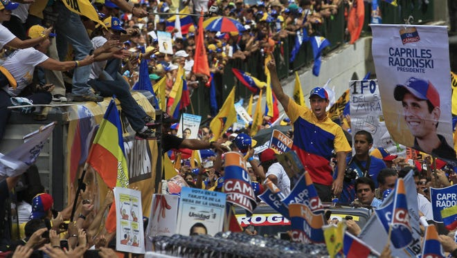 Opposition presidential candidate Henrique Capriles, center, gestures to supporters during a campaign rally in Caracas, Venezuela, Sept. 30. Presidential elections in Venezuela are scheduled for Oct. 7.