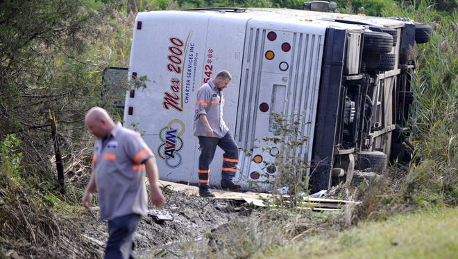 Workers check out a bus which overturned coming off at an exit ramp on Route 80 in Wayne, N.J., on Saturday.