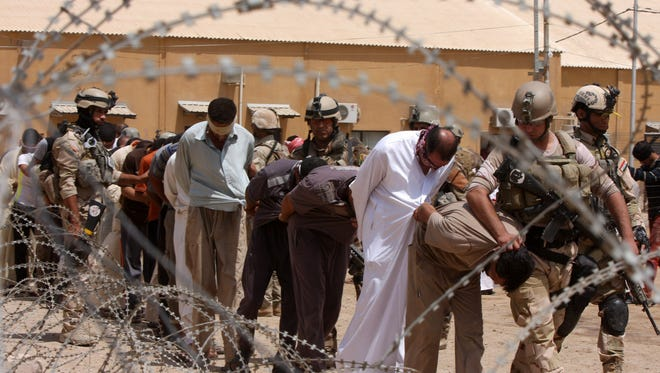 Blindfolded and handcuffed suspected al-Qaeda members are led away to detention centers in an Iraqi army base in Hillah, Iraq, on July 20.
