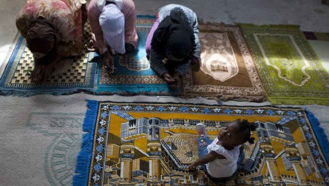 Christine Brazile sits while her relatives pray during Friday prayer service at the Al-Fattah Mosque in Gressier, Haiti.