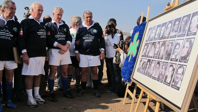 Former members of Uruguay's rugby team who survived a 1972 plane crash in the Chilean Andes hold a moment of silence after the unveiling a plaque with pictures of family members and friends who died in the crash.