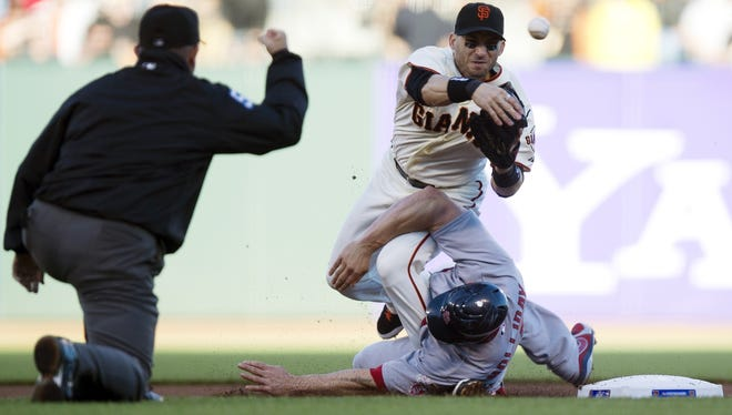 Giants second baseman Marco Scutaro throws to first as he is taken out by the Cardinals' Matt Holliday in Game 2.