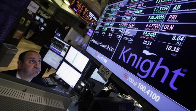 Specialist Peter Giacchi looks at the price of Knight on the floor of the New York Stock Exchange Aug. 1, 2012.