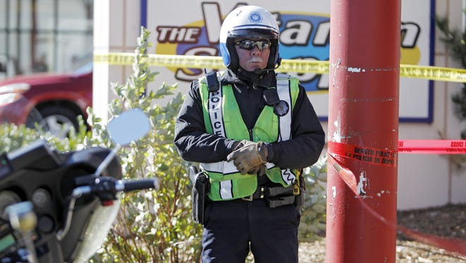A Denver Police officer stands watch at Fero's Bar and Grill in Denver on Wednesday.