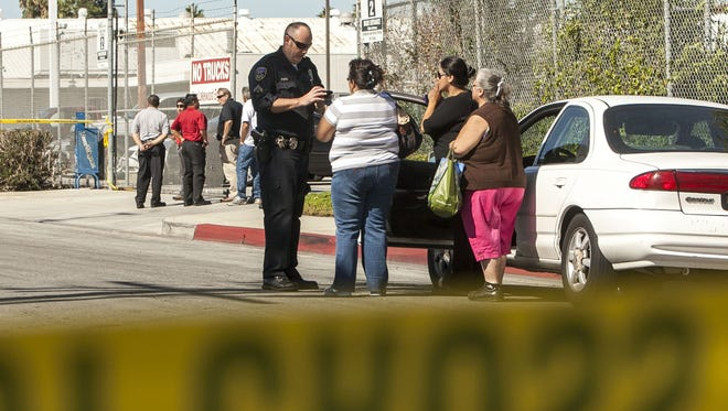 Investigators talk to people across the street from a family-owned business United States Fire Protection Services in Downey, Calif., Wednesday.