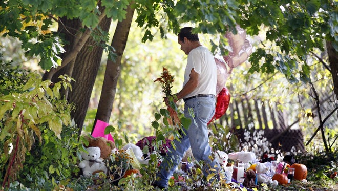 A man places flowers at a shrine for Autumn Pasquale on Wednesday in Clayton, N.J., near where the missing 12-year-old girl's body was found.