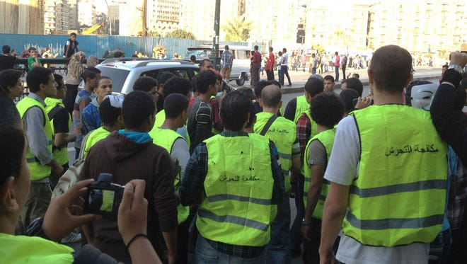Wearing vests painted with the slogan 'Anti-harassment', a group of volunteers confront a group of teasing young boys near Cairo's Tahrir Square.