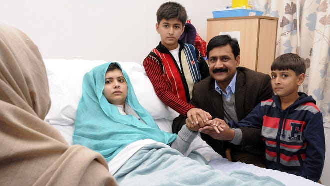 Malala Yousufzai in her hospital bed, poses for a photograph, with her father Ziauddin, second right accompanied by her two younger brothers Atal, right and Khushal, center.