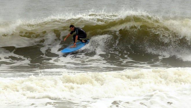Surfers enjoy the waves along Pleasure Island, N.C., on Friday thanks to Hurricane Sandy.