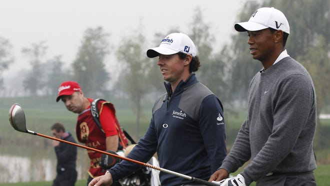 Tiger Woods of the United States, right, and Rory McIlroy of Northern Ireland walk together during their 18-hole medal-match at the Lake Jinsha Golf Club on Monday in Zhengzhou, China.