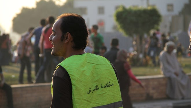 A  volunteer wearing a vest printed with the text anti-harassment monitors Cairo's Tahrir Square.