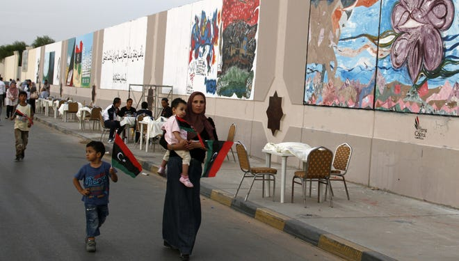 A Libyan family in Tripoli walk by a mural exhibition celebrating one year since the fall of Gadhafi in Tripoli.