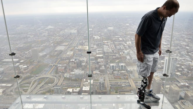 "Zac Vawter, fitted with an experimental ""bionic"" leg, looks down from the Ledge at the Willis Tower in Chicago."