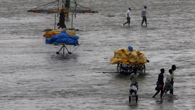 People walk on the Marina beach after it is flooded with sea water on the Bay of Bengal coast in Chennai, India.