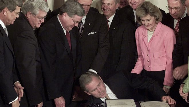 Former President Bush leans over to pick up a pen as he signs his $1.35 trillion tax cut bill in June 2001.