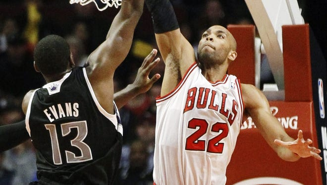 Bulls forward Taj Gibson challenges Kigns guard Tyreke Evans during their season opener Wednesday.