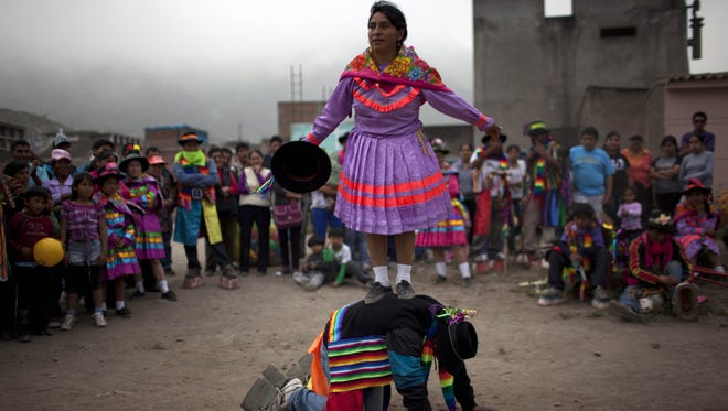Artists perform an indigenous dance called Huaylia at the Virgen de Lourdes cemetery where relatives converge to honor friends and family who have passed, marking the Day of the Dead holiday in Lima, Peru, Thursday.